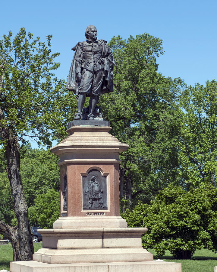 Statue of William Shakespeare in Tower Grove Park. Pictured is a statue of William Shakespeare standing with a heavy coat draped over his shoulders and in his stock image