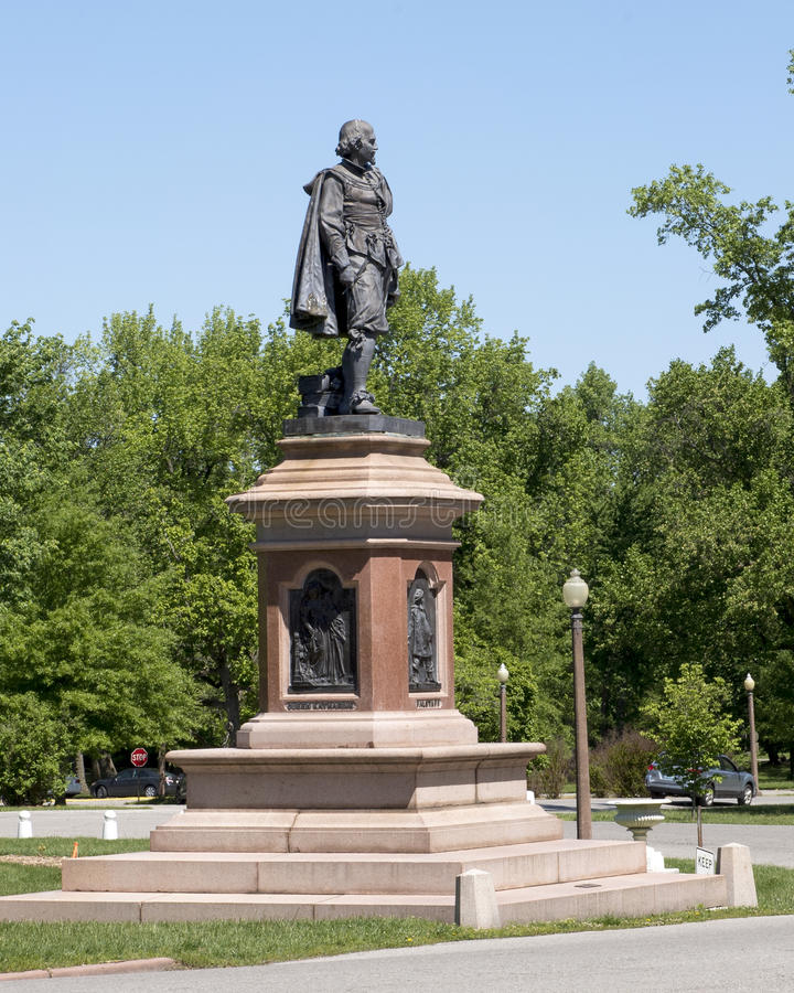 Statue of William Shakespeare in Tower Grove Park. Pictured is a statue of William Shakespeare standing with a heavy coat draped over his shoulders and in his stock photography