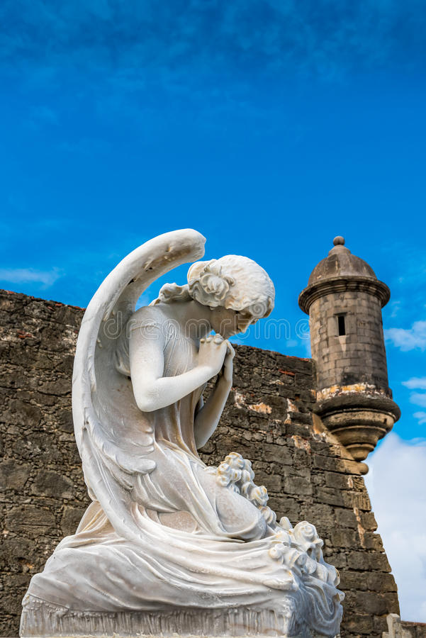 Statue of a winged angle kneeling at a grave. With fortress turret in the background stock photo
