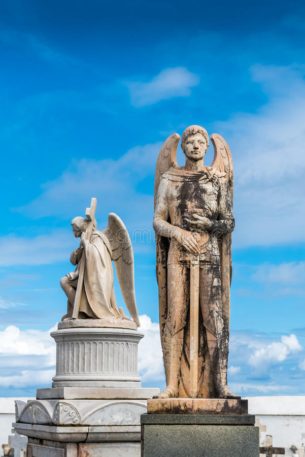 Statue of a winged man with sword on a grave. With another winged man holding a cross in the background stock images