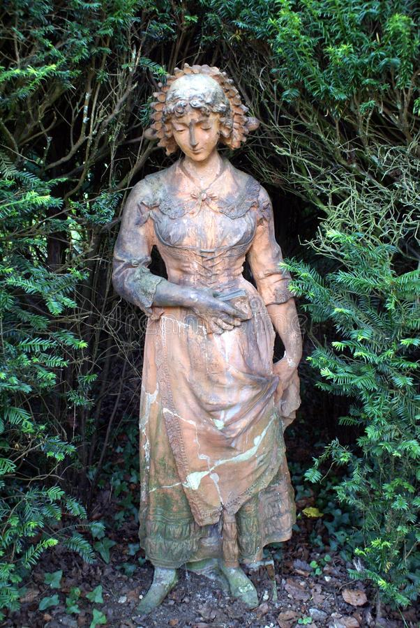 Statue of a woman carrying a book. Garden decoration of a statue of a woman carrying a book stock photo
