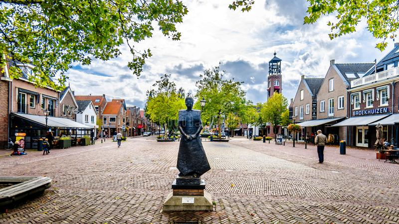 Statue of a woman in traditional dress in Bunschoten-Spakenburg in the Netherlands. Statue of a woman in traditional dress in the historic fishing village of royalty free stock image