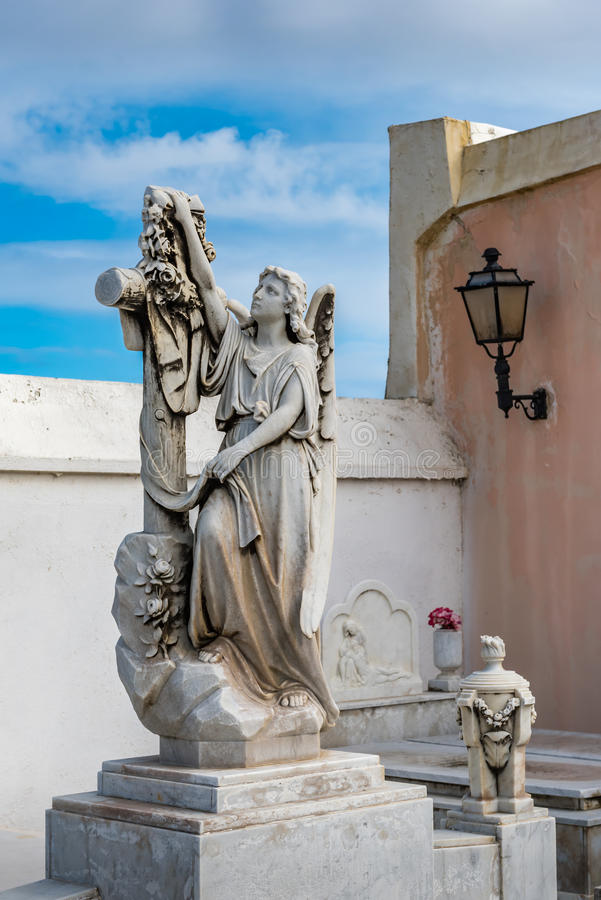 Statue of a women drapping a cross with a cloth. On top of a grave stock images