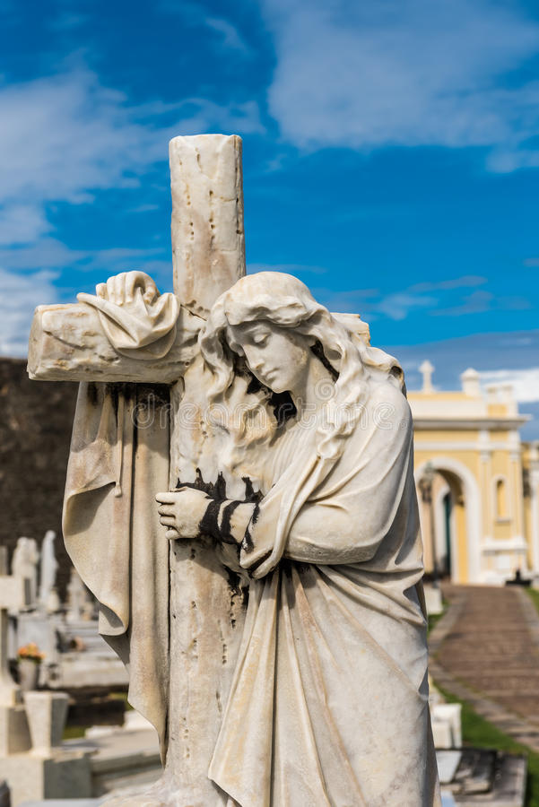Statue of a women hugging a cross. On a grave site stock image