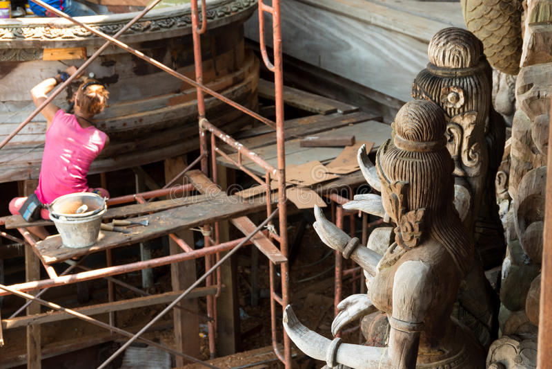 Statues bouddhistes en bois avec le dépanneur à l'arrière-plan au site de restauration sur l'extérieur de côté du sanctuaire de l photographie stock libre de droits