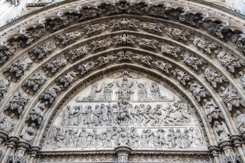 Statues in bow above entrance to cathedral, Antwerpen, Belgium. Antwerpen, Belgium - June 23, 2019: Closeup of beige stone bow full of statues above the main royalty free stock photo