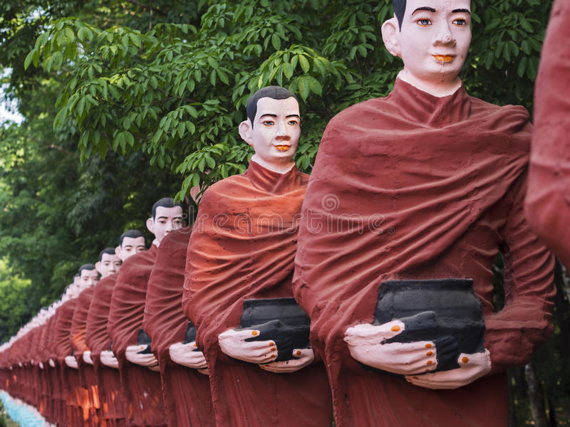 Statues of Buddhist Monks in Mawlamyine, Myanmar. Statues of Buddhist monks collecting alms surround the massive Win Sein Taw Ya Buddha, the largest Reclining royalty free stock photography