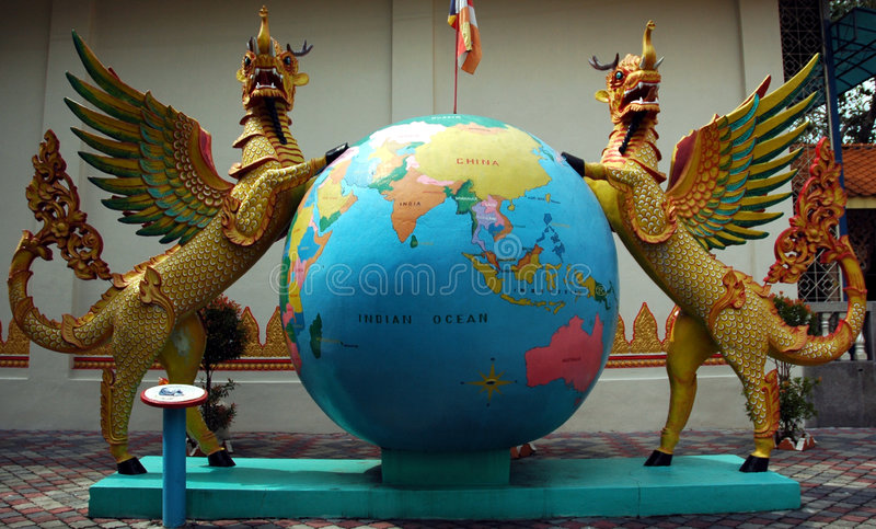 Statues in burmese temple. 2 beast like statue standing on a globe in a burmese temple royalty free stock photography