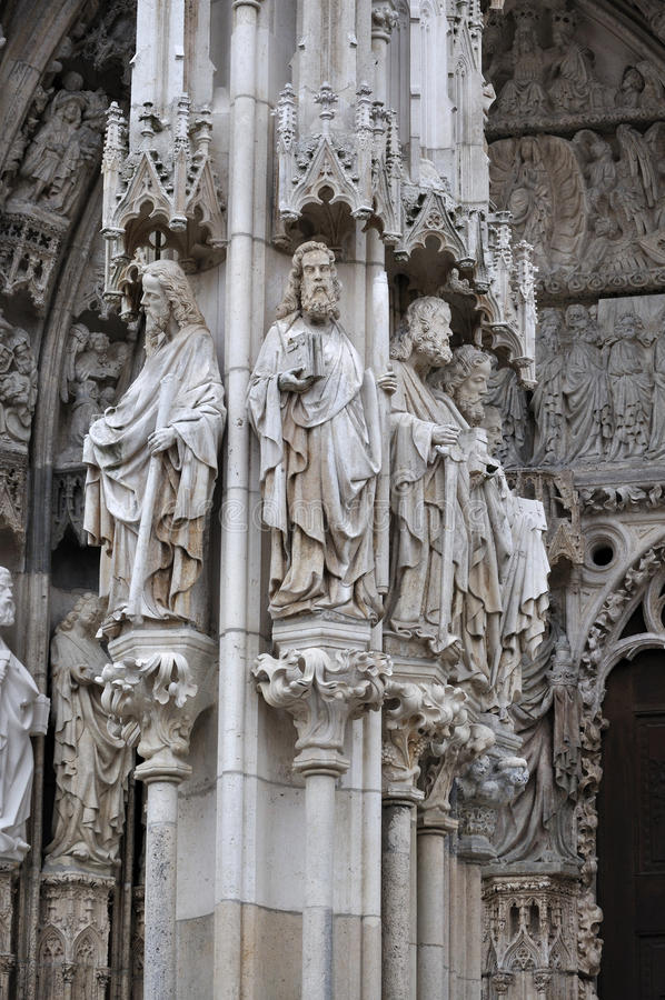 Statues at cathedral, regensburg. Detail of the main portal of the cathedral with medieval grey stone statues of saints royalty free stock photo