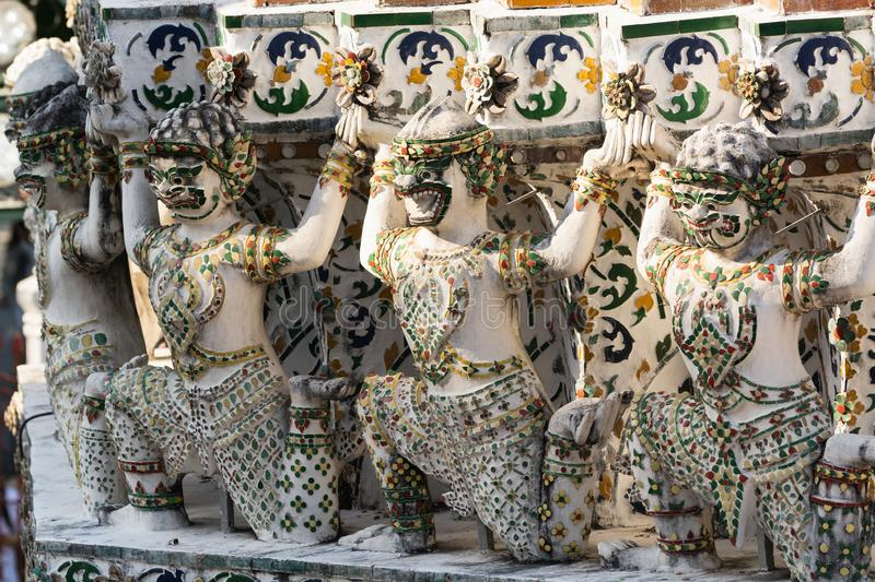 Statues at the facade of Wat Arun temple roof on a sunny day in Bangkok, Thailand stock photo