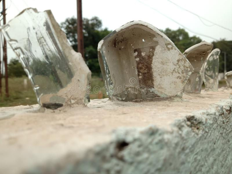 Statues of glass pieces on a concrete boundary. Glass pieces mounted on a concrete boundary with blurry background royalty free stock photo