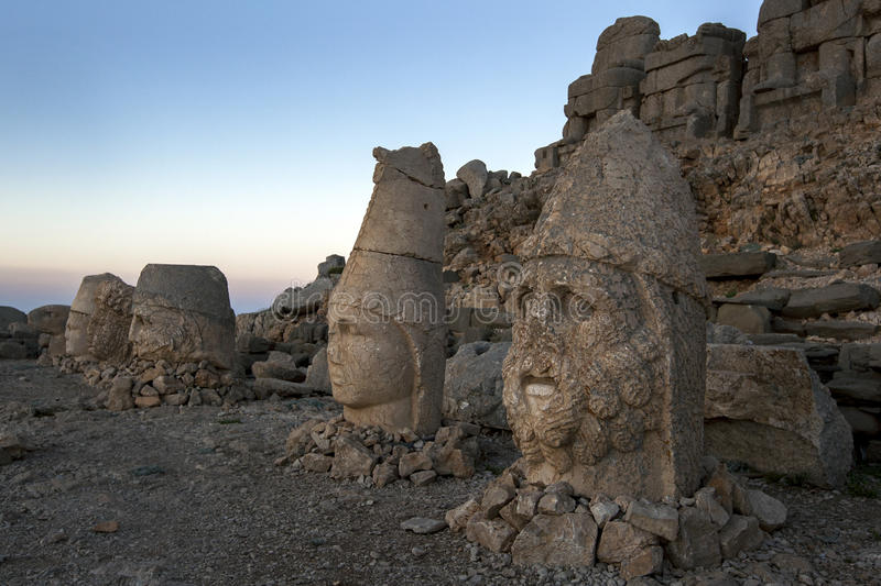 Statues of goddess Tyche of Commagene far left, Zeus, Antichos and Hercules on the eastern platform at Mt Nemrut in Turkey. Statues of goddess Tyche of stock photography