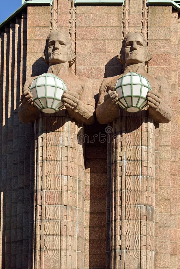 Statues holding the spherical lamps at the Helsinki Central railway station royalty free stock photos