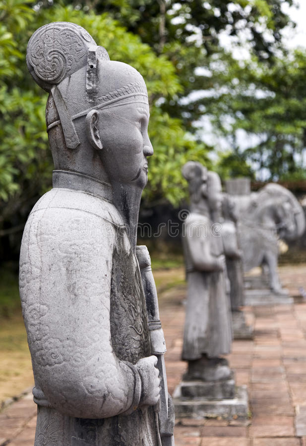 Statues at Minh Mang Tombs. Ancient statues carved from stone stand in front of the entrance to Minh Mang Tomb near Hue in Vietnam royalty free stock image