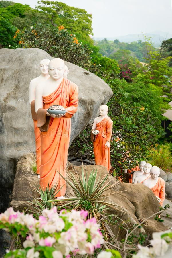 Statues of monks in Golden cave temple in Dambulla, Sri Lanka. Statues of monks on a rock with flowers in Golden cave temple in Dambulla, Sri Lanka stock image
