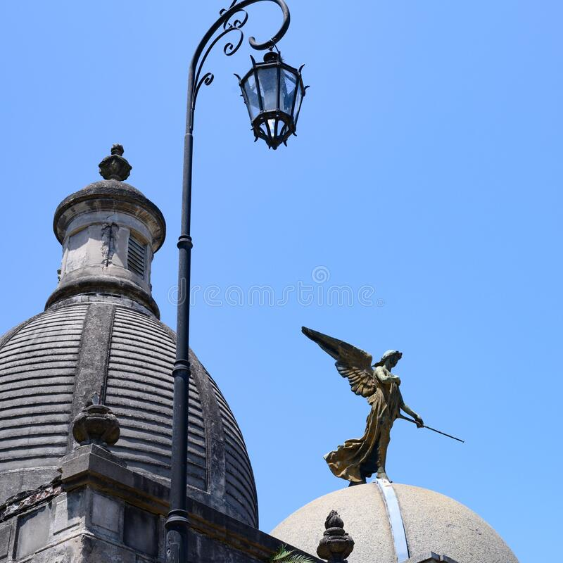 Domes, iron lamp and angel on La Recoleta Cemetery, Buenos Aires. Argentina. Statues and monuments on graves at La Recoleta Cemetery, Buenos Aires, Argentina stock image