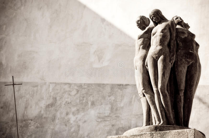 Statues of nude women. Statue of four nude women back to back on plinth with old wall in background royalty free stock image