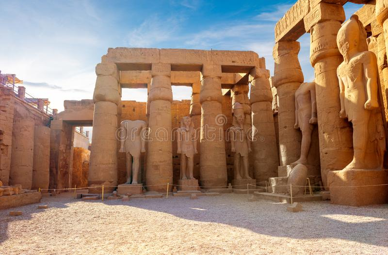 Statues in Karnak temple. Statues of pharaoh in Karnak temple of Luxor at sunrise royalty free stock photography