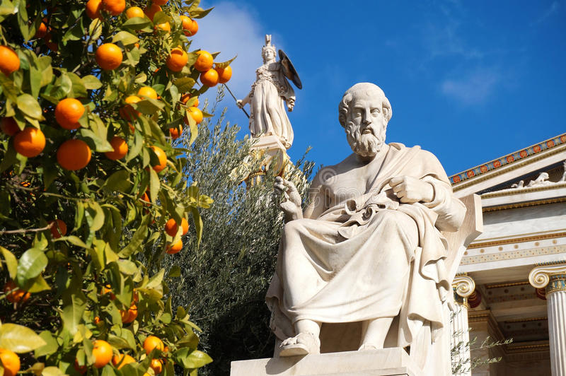 The Statues of Plato and Athena at the Academy of Athens. The Statues of Plato and Goddess Athena at the Academy of Athens by Orange and Olive Trees under the stock photos