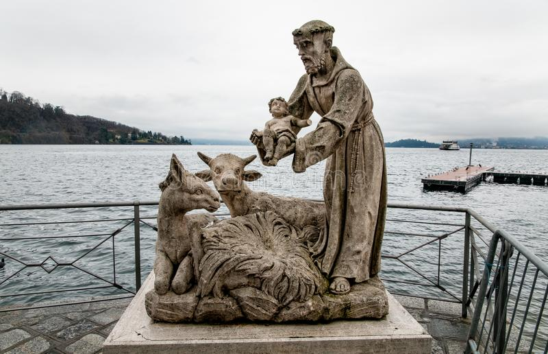 Statues of Saint Francis with Jesus child on Lake Maggiore in Laveno Mombello, Italy.  royalty free stock image
