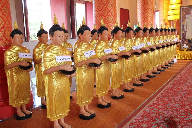 Statues in a Thai temple. Holding bowls for donations to be deposited into stock photo