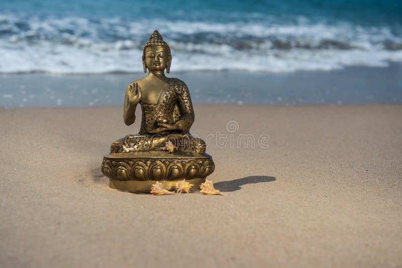 Statuetta bronzea Buddha sulla spiaggia con le onde fotografia stock