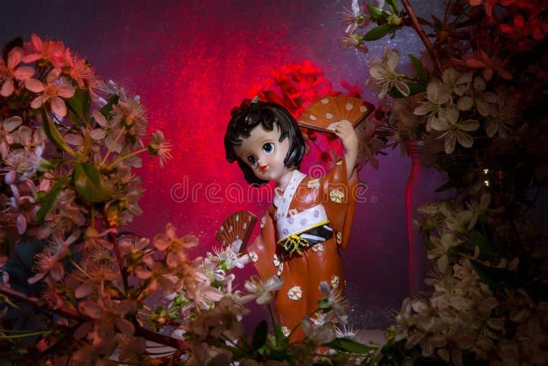 Statuette dancing geisha in the garden. Sakura with decorative lighting royalty free stock image