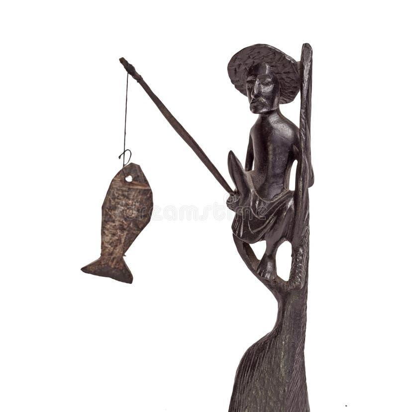 Statuette des Fischers sitzend auf Stapel mit Fischen stockbild