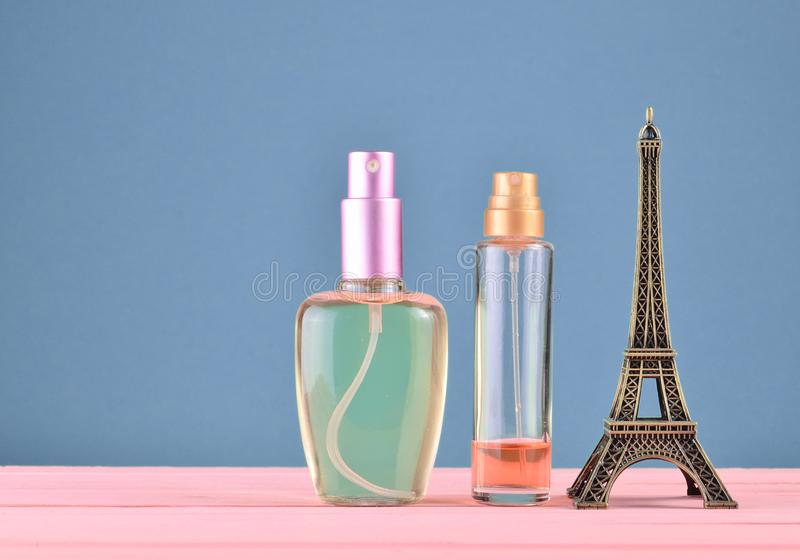 A statuette of the Eiffel Tower, bottles of perfume on a blue pastel background, minimalist trend, space for text, beauty. And fashion concept stock photography