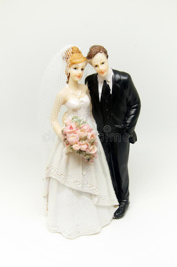 Statuette in the form of a newly-married couple. On white background royalty free stock photo