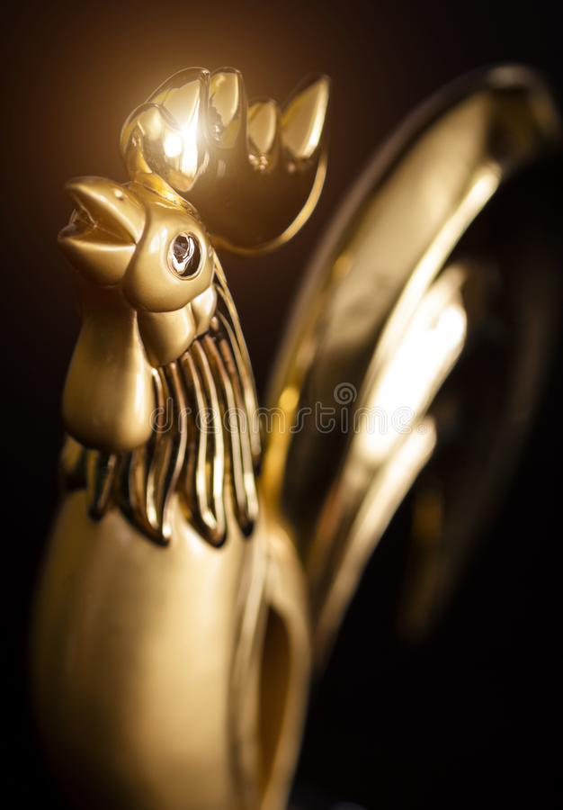 The statuette of the golden rooster. Statuette of a golden rooster on a black background close-up royalty free stock photography