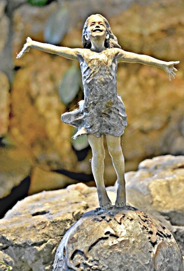 Statuette of a joyful little girl in a rock garden royalty free stock images