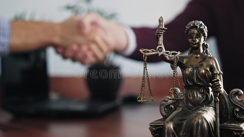 Statuette of lady justice on the table close-up. On a blurred background of two men handshaking royalty free stock photos