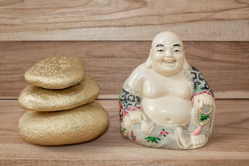 Statuette of laughing Buddha with stones, on a wooden background, Feng Shui. stock photos