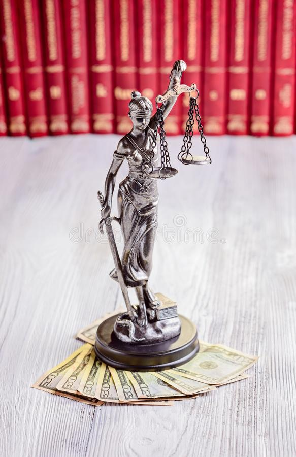 Statuette of Themis and american dollars. In court library. Bribe and law concept royalty free stock images