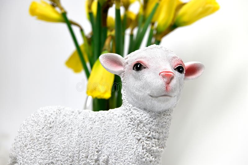 Statuette of a white lamb with a pink coloured nose in front of a vase with yellow daffodils stock image