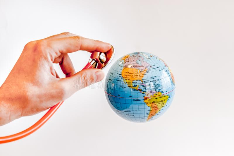 STATUS OF HEALTH OF THE PLANET. A DOCTOR VISITS WITH A FONENDO THE EARTH TO CHECK YOUR HEALTH STATUS IN A WHITE BACKGROUND royalty free stock image
