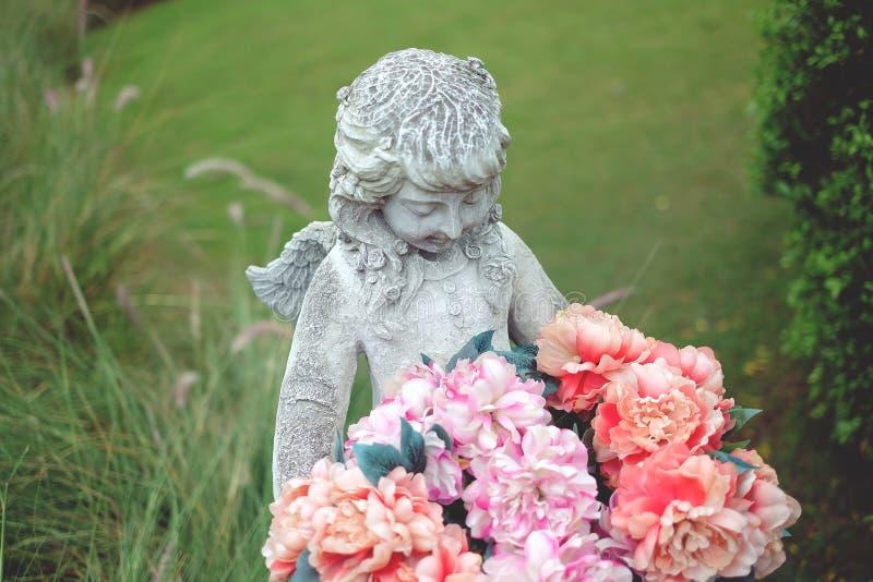 Statyänglar och blomma i trädgård fotografering för bildbyråer