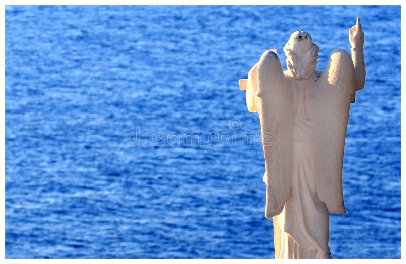 Staty av ängeln med det blåa havet i backround royaltyfri foto