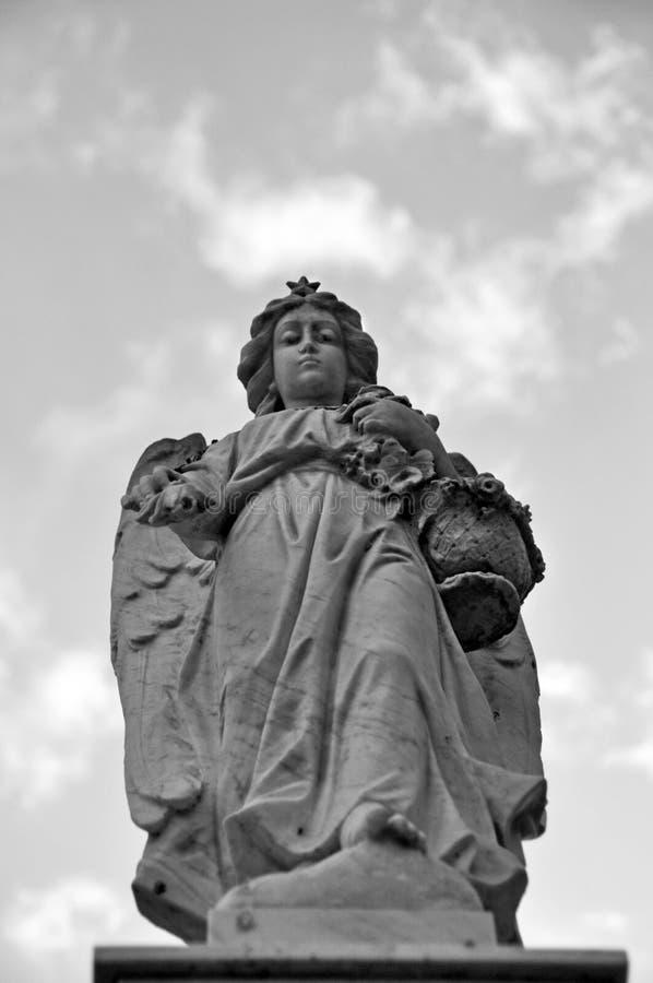 Staty av ängeln som ser ner i kyrkogård i svartvitt arkivbild
