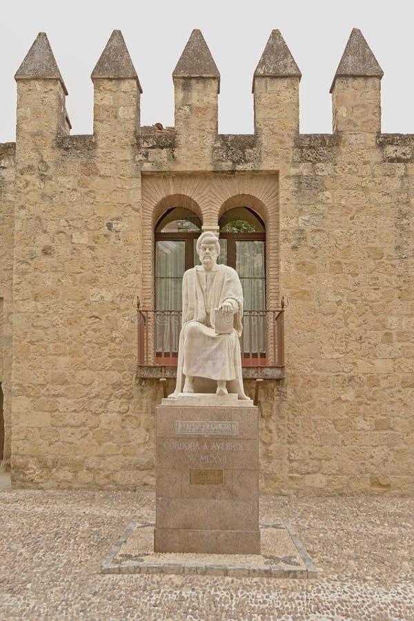 Staty av averroes framme av den romerska stadsväggen av Cordoba royaltyfri fotografi