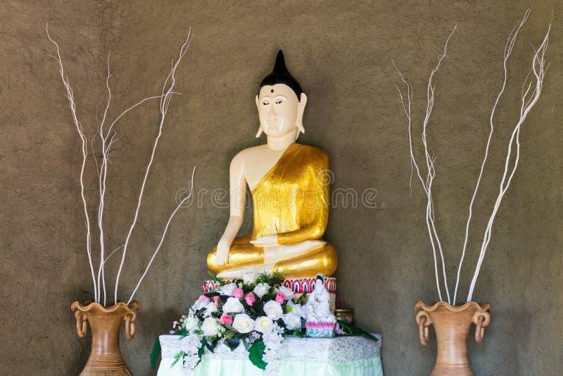 Staty av Buddha med den grova cementväggen arkivfoto