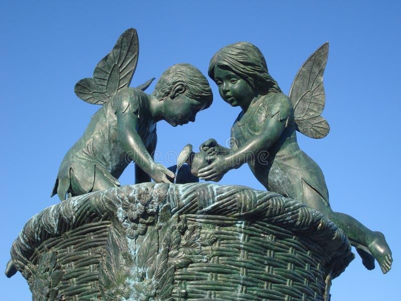 Staty av den bevingade lilla flickan och pojken arkivbild
