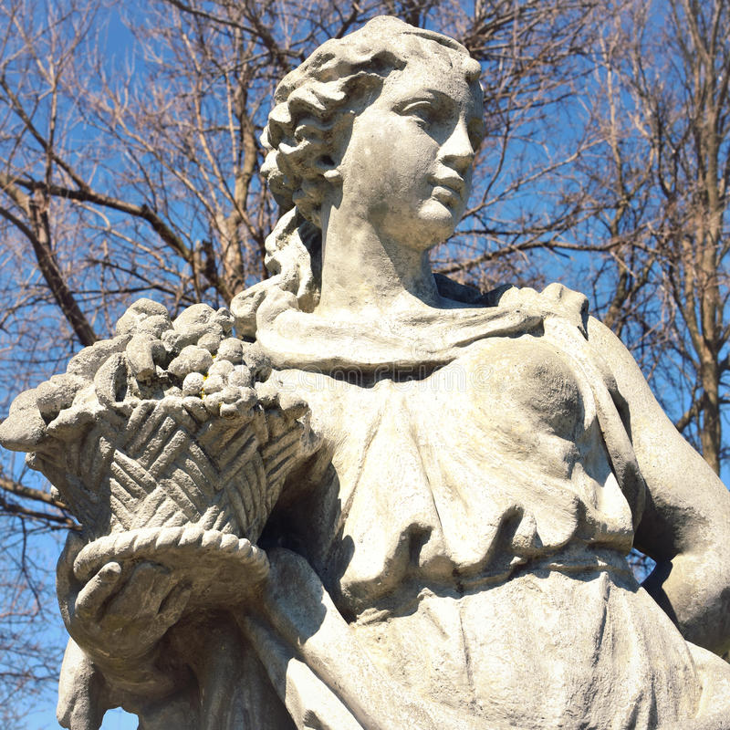Staty av den hållande korgen för kvinna av frukt royaltyfria foton