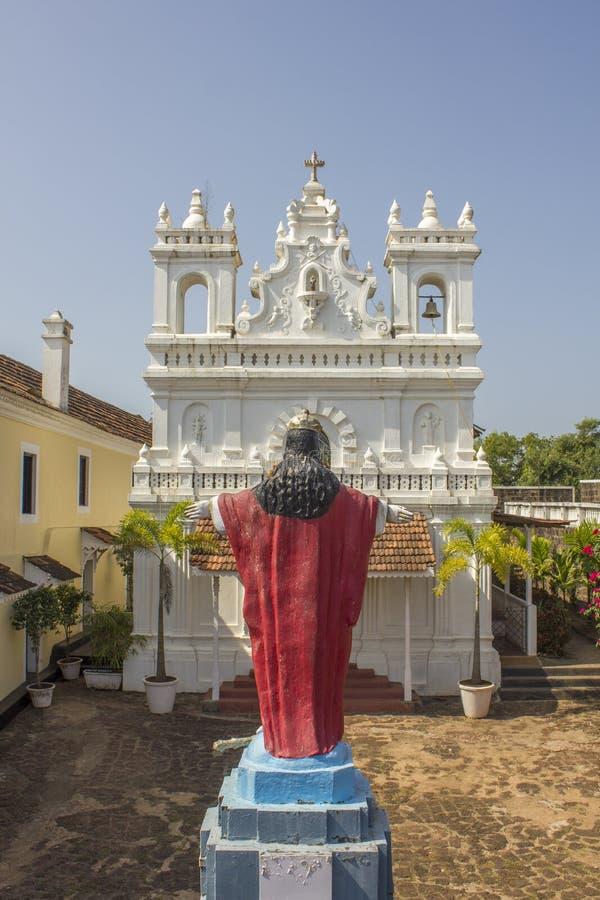 Staty av den Jesus Christ sikten från baksidan på bakgrunden av den vita katolska kyrkan arkivbilder