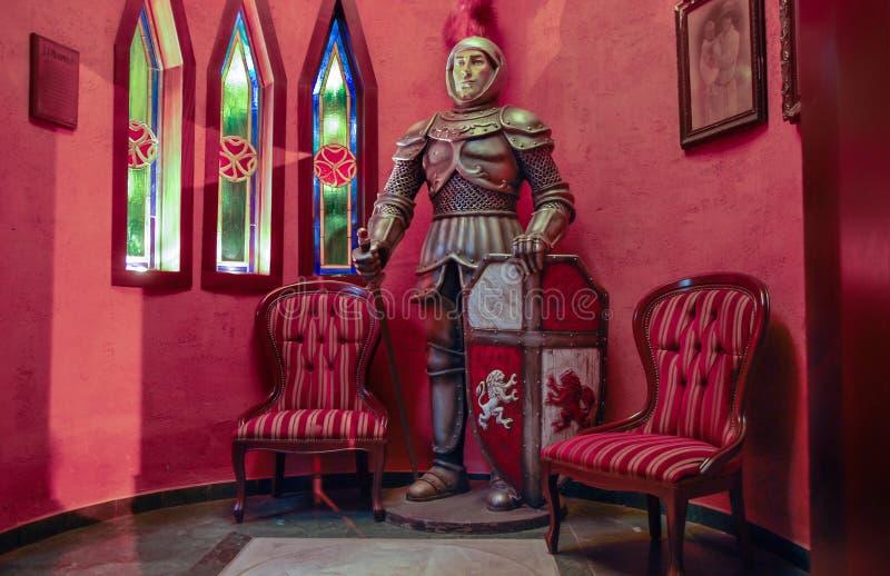 Staty av den oavkortade harneskställningen för medeltida riddare i ett kaféhörn royaltyfri bild