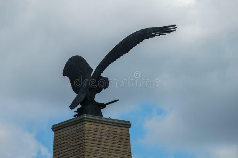 Staty av en örn med öppna vingar mot en molnig molnig himmel arkivbild