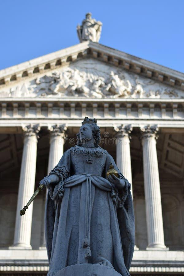 Staty av en drottning med frontonen av en domkyrka i bakgrunden i London royaltyfri foto