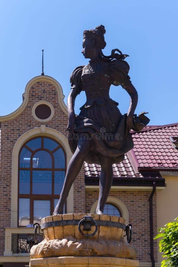 Staty av en flicka på en trätrumma på bakgrunden av ett hus med figurerade exponeringsglas arkivbild