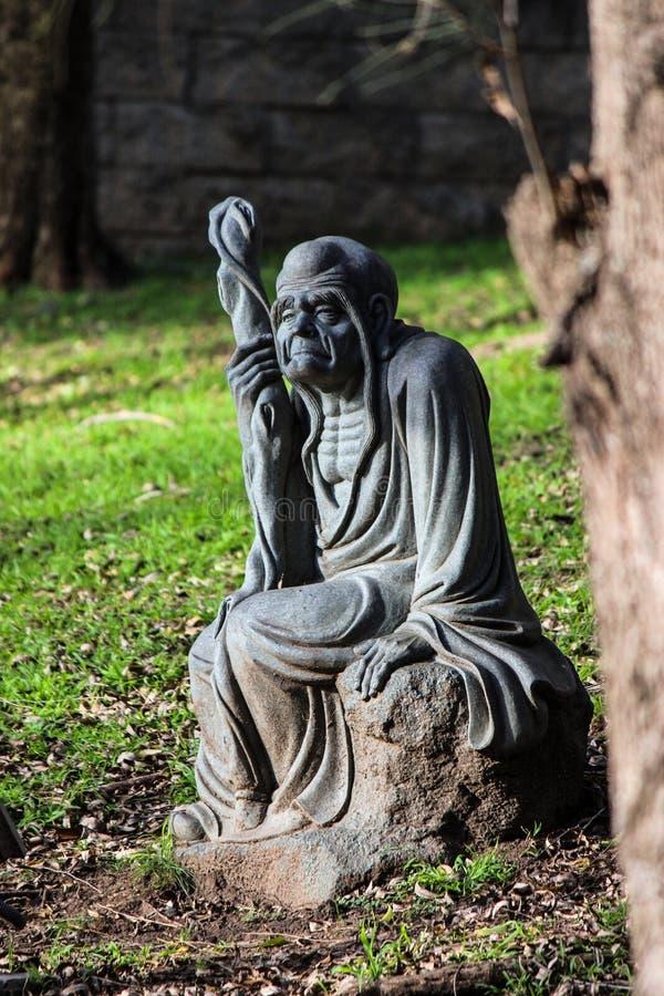 Staty av en gamal man som sitter på en vagga i trädgården av Nan Tien Temple, Wollongong, Australien arkivfoto